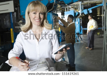 Smiling woman using calculator and checking newspaper with colleagues in factory - stock photo