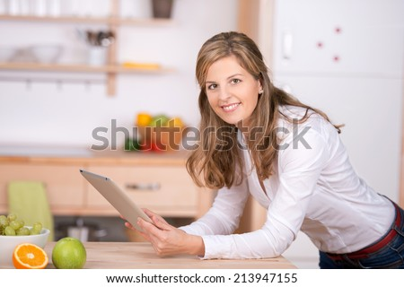 smiling woman using digital pad in the kitchen - stock photo