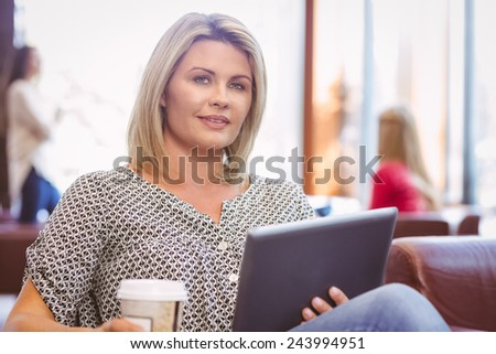 Smiling woman using digital tablet and holding disposable cup in library - stock photo