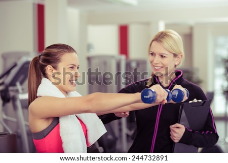 Smiling Woman Using Hand Weights While Personal Trainer Supervises Her Progress - stock photo
