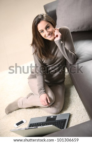 Smiling woman using her laptop in the living room. - stock photo