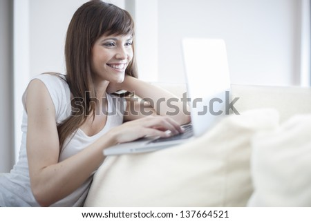 Smiling woman using her laptop sitting on the couch in her home. She is looking at laptop and smiling - stock photo