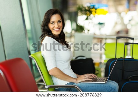 smiling woman using laptop at airport while waiting for her flight - stock photo