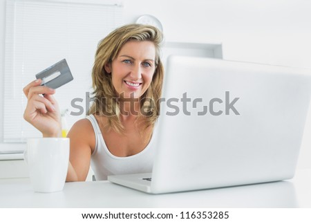 Smiling woman using laptop for online shopping