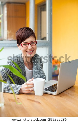 Smiling woman using laptop in coffee shop. Work and pleasure concept.