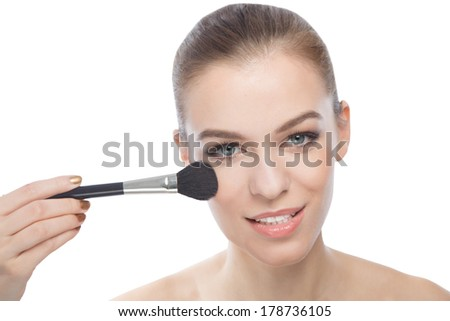 Smiling woman using make-up brush, doing her make-up or some touch ups. - stock photo