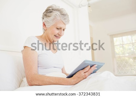 Smiling woman using tablet sitting on the bed - stock photo