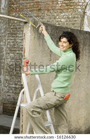 Smiling woman using tools. Vertically framed photo.