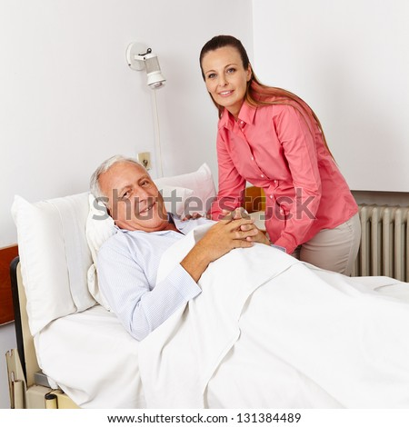 Smiling woman visiting old bedridden man in a hospital bed - stock photo