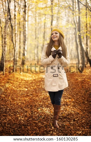 Smiling woman walking in park at autumn season  - stock photo