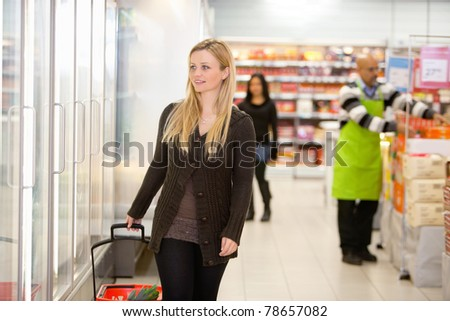 Smiling woman walking in shopping centre, looking in refrigerator with people in the background - stock photo