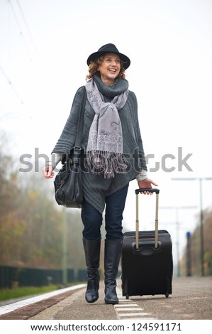 Smiling woman walking on train station platform with travel bag - stock photo