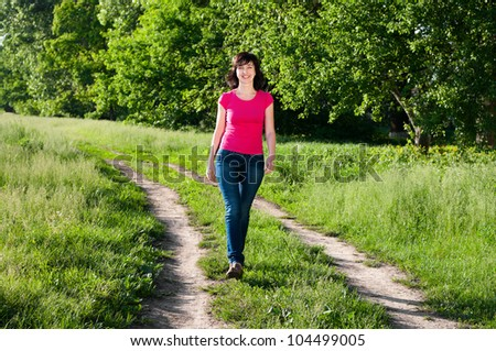 Smiling woman walking outdoors on the forest road in summer - stock photo