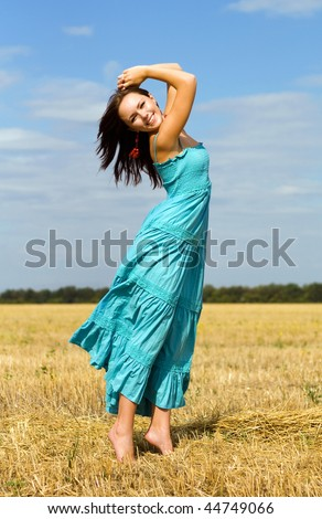 Smiling woman wearing blue dress in the field - stock photo