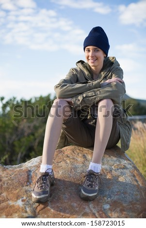 Smiling woman wearing cap sitting on a rock looking at camera in the countryside - stock photo