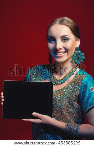 Smiling woman wearing traditional Indian sari with accessories- earrings, bracelets and rings and mehndi henna tattoos showing blank black digital tablet screen - stock photo