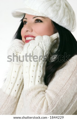Smiling woman wearing winter hat gloves and polo neck jumper. - stock photo