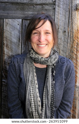 Smiling woman with a barn wood background. - stock photo