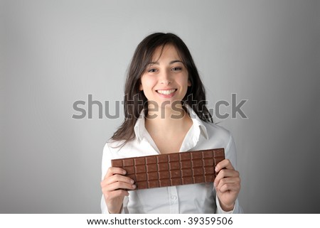 smiling woman with a big chocolate bar - stock photo