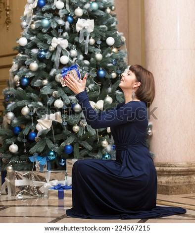 Smiling woman with a Christmas present - stock photo