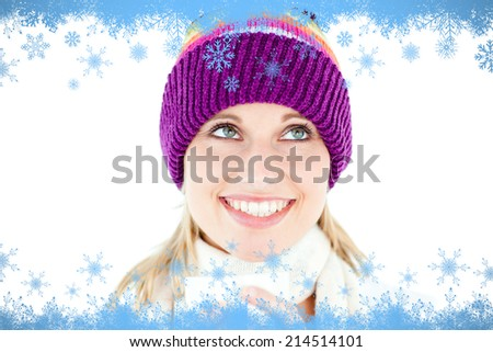 Smiling woman with a colorful hat and a cup in her hands against snow flake frame in blue