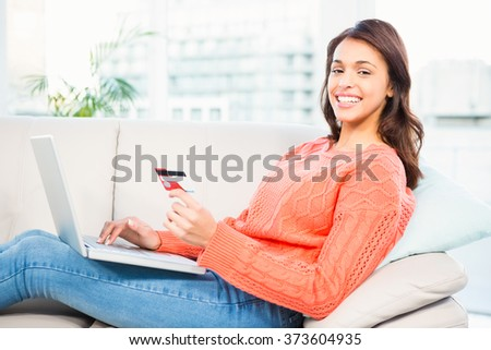 Smiling woman with a credit card and a laptop on a sofa at home - stock photo
