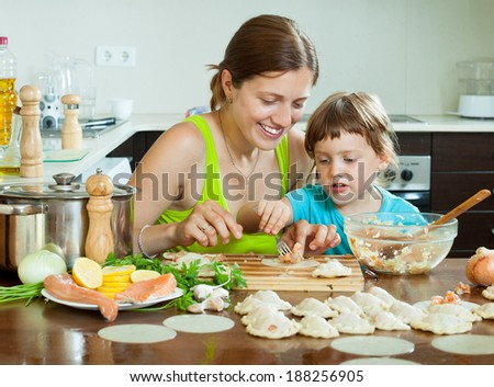 Smiling woman with a happy child makes Fish dumplings with salmon on the inside of the kitchen