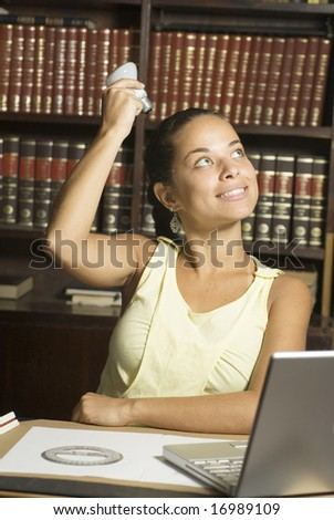 Smiling woman with a lightbulb over her head as she sits at a desk with a laptop and a compass. Vertically framed photo. - stock photo