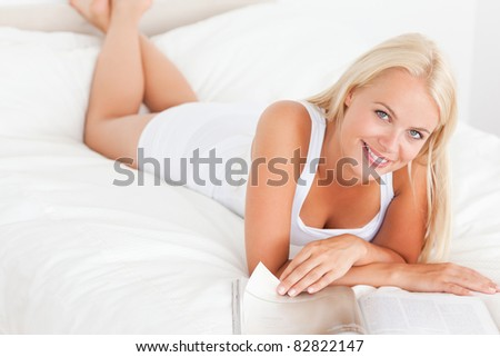Smiling woman with a magazine in her bedroom - stock photo