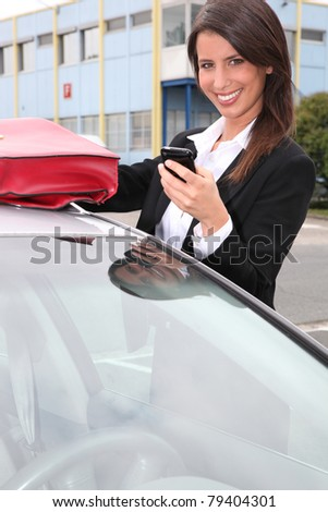 Smiling woman with a phone by her car - stock photo