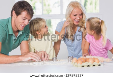 Smiling woman with a rolling pin in hands in kitchen