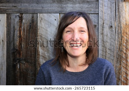 Smiling woman with a rustic wood background. - stock photo