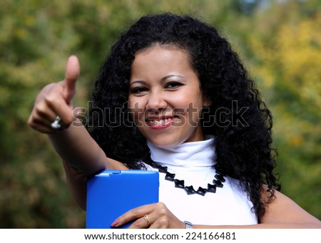 Smiling woman with a tablet showing thumb up, outdoor. Ok sign. (focus on face)