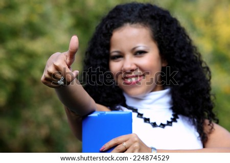 Smiling woman with a tablet showing thumb up, outdoor. Ok sign. (focus on hand) - stock photo