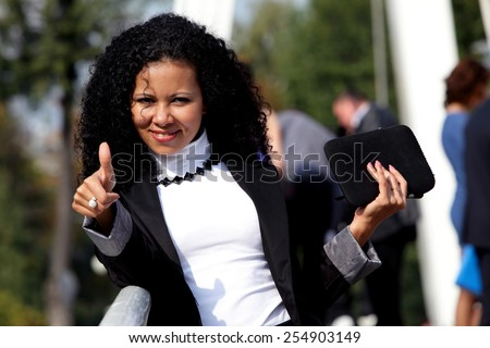 Smiling woman with a tablet showing thumb up, outdoor. Ok sign. (focus on hand)
