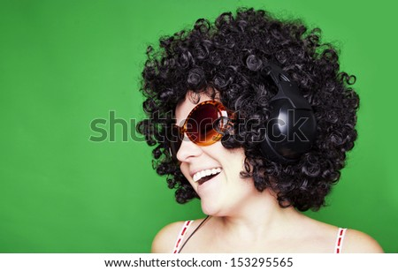 smiling woman with afro hair listen to music with headphones  over green background - stock photo
