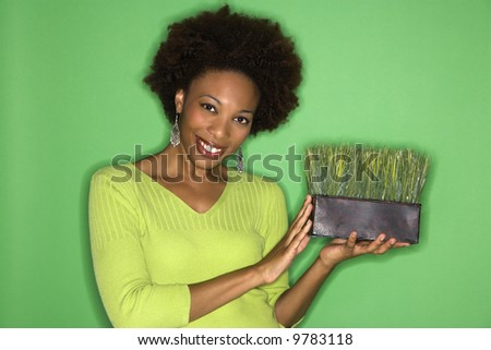 Smiling woman with afro holding pot of grass against green background.