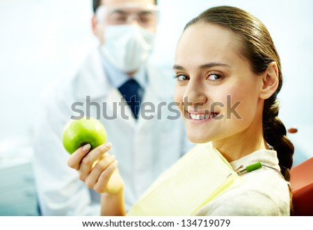Smiling woman with apple looking at camera with dentist on background - stock photo