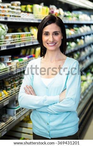 Smiling woman with arms crossed in supermarket - stock photo
