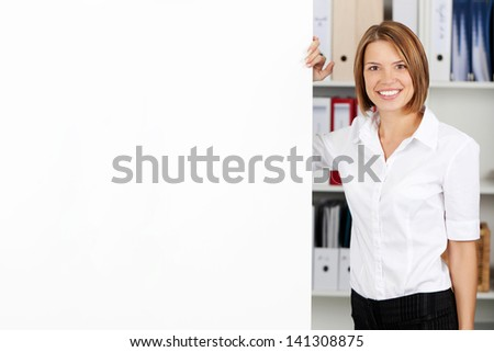 Smiling woman with blank white flipchart while standing alongside it in the office - stock photo