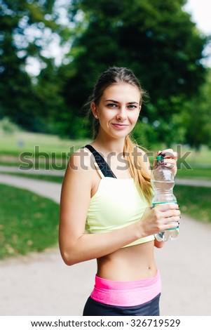 Smiling woman with bottle of water outdoor