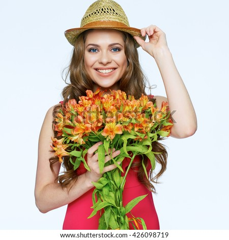 Smiling woman with bouquet flowers standing over white isolated background. Female portrait.