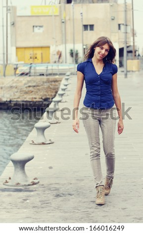 smiling woman with camera outdoors - stock photo