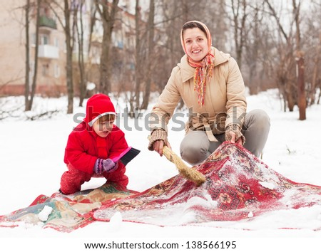Smiling woman with child cleans rug with snow in winter day - stock photo