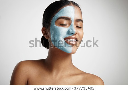 smiling woman with closed eyes and a half a face with a mask - stock photo