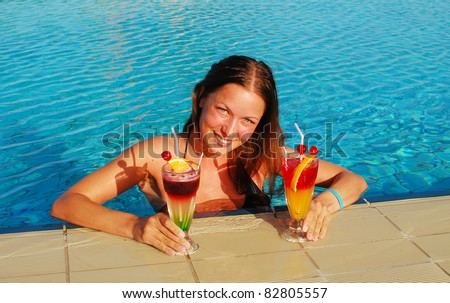 smiling woman with cocktails in the pool