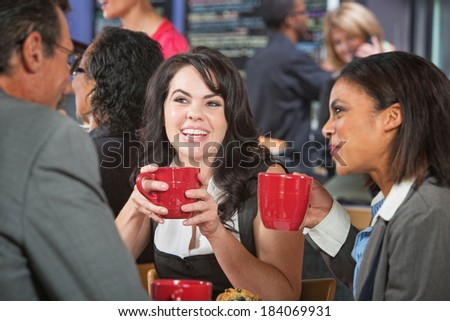 Smiling woman with coffee and friends in bistro - stock photo