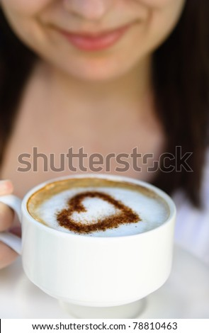 Smiling woman with cup of coffee decorated with heart - stock photo