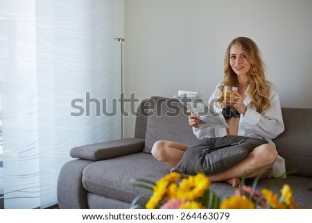 smiling woman with cup of coffee reading magazine at home - stock photo