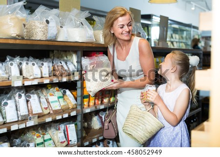 smiling woman with daughter buying various cereals in grocery store - stock photo